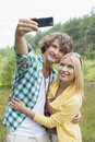 Happy young couple taking self portrait through cell phone in field Royalty Free Stock Photos