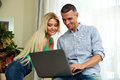 Happy young couple using laptop at home Royalty Free Stock Photo