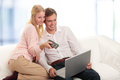 Happy young couple using laptop in living room Royalty Free Stock Photo