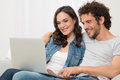 Happy young couple using laptop portrait of sitting on sofa pc Royalty Free Stock Images