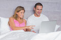 Happy young couple using their laptop together in bed at home bedroom Royalty Free Stock Photo