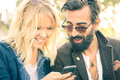 Happy young couple with vintage clothes having fun with phone Royalty Free Stock Photo