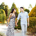 Happy young couple walking together in a green park outdoors Stock Photos
