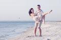 Happy young couple in white clothing have romantic recreation and fun at beautiful beach on vacations Royalty Free Stock Photography