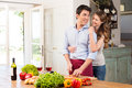 Happy young couple working in kitchen beautiful woman embracing man Royalty Free Stock Photo