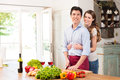 Happy young couple working in kitchen beautiful woman embracing man Stock Photo