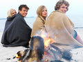 Happy young couples sitting by bonfire at beach Royalty Free Stock Images
