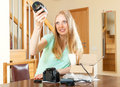 Happy young cute woman unpacking new digital camera at home Royalty Free Stock Image