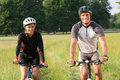 Happy young cyclists couple two cyclist in field riding bicycle Stock Photography