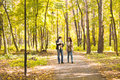 Happy young family in the autumn park outdoors on a sunny day. Mother, father and their little baby boy are walking in Royalty Free Stock Photo