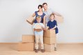 Happy young family carrying boxes Stock Photography