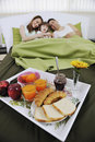 Happy young family eat breakfast in bed Royalty Free Stock Photo