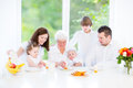 Happy young family enjoying easter breakfast with three children teenager boy toddler girl and a newborn baby with their Royalty Free Stock Photo