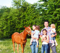 Happy young family with four children and baby horse in the spring forest Stock Photography