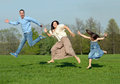 Happy young family games in nature jumping on the Stock Photography