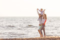Happy young family have fun on beach run and jump at sunset Royalty Free Stock Photo