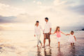 Happy young family have fun walking on beach at sunset Royalty Free Stock Images