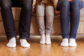 Happy young family large and small feet sitting on sofa together focus on feet s feet close up on wood floor Royalty Free Stock Images