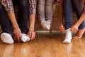 Happy young family large and small feet sitting on sofa together focus on feet s feet close up on wood floor Stock Photos