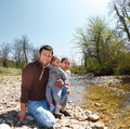 Happy young family with little daughter near the mountain river outdoors Royalty Free Stock Images