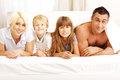 Happy young family lying on the bed and looking at camera Royalty Free Stock Photos