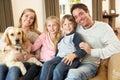 Feliz joven familia en sofá perro
