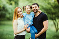 Happy young family spending time together in green nature. wife with husbend and daughter. Mother and father holding daughter in p