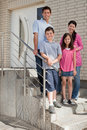 Happy young family standing at doorstep Stock Image