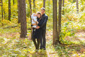 Happy young family with their daughter spending time outdoor in the autumn park Royalty Free Stock Photo