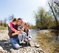 Happy young family with two little daughters near the mountain r river outdoors Stock Photography