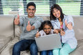 Happy young family using laptop with thumbs up Royalty Free Stock Photo