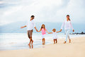 Happy young family walking on the beach at sunset lifestyle Stock Images