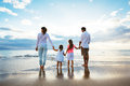 Happy young family walking on the beach at sunset lifestyle Royalty Free Stock Photo