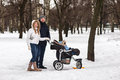Happy young family walking in the park in winter Royalty Free Stock Photo