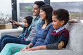 Happy young family watching tv in living room Royalty Free Stock Image