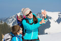 Happy young family in winter vacation smartphone selfie