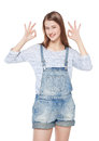 Happy young fashion girl in jeans overalls gesturing okay isolat isolated on white background Stock Photo