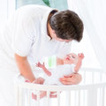 Happy young father putting his newborn baby in crib a white with canopy Royalty Free Stock Photography