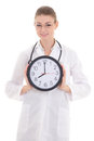 Happy young female doctor holding office clock isolated on white background Stock Photos