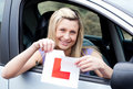 Happy young female driver tearing up her L sign Royalty Free Stock Photography