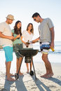 Happy young friends having barbecue together on the beach Stock Photos