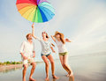 stock image of  Happy young friends jump with colourful umbrella