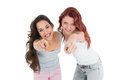 Happy young friends pointing against white background portrait of two female Royalty Free Stock Images
