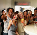 Happy young friends saying cheers at a bar Stock Photos