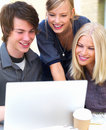 Happy young friends using laptop Royalty Free Stock Photos