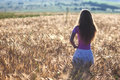 Happy young girl in golden wheat field. Young woman enjoying nat Royalty Free Stock Photo