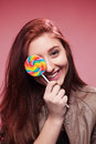 Happy young girl with lollipop on a pink portrait of the teenager sugar candy stick background Royalty Free Stock Photography