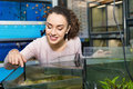 Happy young girl looking at tropical fish