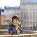 Happy young girl in paris with tulips a bunch of fresh beautiful Stock Photos