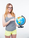 Happy young girl pointing finger on world globe